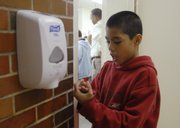 Kennedy School student Truman LeFlore, 10, cleans his hands Wednesday before lunch, using a hand sanitizer from a wall dispenser. Lawrence schools have installed the dispensers as a way to combat the spread of germs and promote personal hygiene.