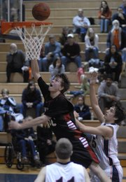 Lawrence High's John Schneider scores on a layup during the Lions' 59-46 loss to Olathe East on Friday at O-East.