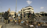Iraqis participate in cleanup at the site of a suicide bombing at a popular pet market Friday in central Baghdad. Two female suicide bomber killed at least 91 people, police said, the deadliest bombing to strike the capital since 30,000 more U.S. troops flooded into central Iraq last spring.