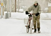 Clyde Wheatfill pushes his bicycle down a snowy street Friday in Lafayette, Ind. Heavy, wet snow made for treacherous roads and delayed commutes Friday as a huge winter storm that stretched from Texas to the Great Lakes blanketed the nation's midsection Friday.