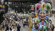 A strand of beads flies from the King's Jesters float during the Rex Mardi Gras parade Tuesday in New Orleans. Carnival revelers were greeted with warm weather for Fat Tuesday.