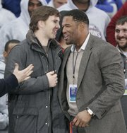 New York Giants quarterback Eli Manning, left, talks with defensive end Michael Strahan after receiving the keys to the city. The Giants were honored with a parade Tuesday in New York.