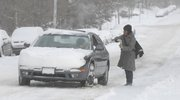 Kansas University student Ruti Patel, Overland Park, coaches a driver on how to get up the hill on Indiana Street without getting stuck in the snow.