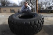 Jacob Linn flipping a tractor tire.