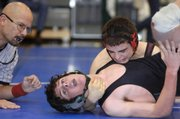 Free State High's Jake Brown, bottom, is seconds away from being pinned by Shawnee Mission North's Andrew Jones during a 135-pound match Saturday at the Sunflower League wrestling meet at Olathe Northwest High.