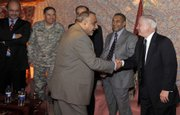 Iraqi Vice President Adil Abd Al-Mahdi, center, and U.S. Secretary of Defense Robert Gates shake hands Sunday during an unannounced visit with Iraqi government officials in this photo provided by the U.S. Department of Defense.