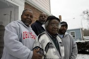 Henry Bolden Jr., second from right, stands in front of his home in the Hanford Village neighborhood with his sons, Will, Hank and Ron, in Columbus, Ohio. With help from the G.I. Bill, Bolden was able to buy his house in 1946 in a neighborhood that doesn't look like much now but was revolutionary in its day: single-family homes marketed solely to blacks. Communities around the country are trying to win historic recognition for these neighborhoods as they age and their place in the history of home ownership fades.