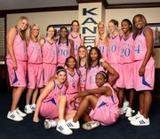 Kansas University's women's basketball team shows off its special pink uniforms. The Jayhawks will wear the unis during their game Sunday against Nebraska to call attention to breast cancer awareness.