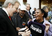 "Australian Prime Minister Kevin Rudd, left, signs a autograph for a Aboriginal woman after delivering a speech in which he apologized to the country&squot;s indigenous people for past treatment that ""inflicted profound grief, suffering and loss,"" Rudd said. In a vote today, Australia&squot;s Parliament apologized to tens of thousands of Aborigines who were forcibly taken from their families as children under now-abandoned assimilation policies."
