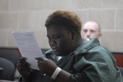 Sherise Spears, 20, Topeka, reads the charges against her during her first appearance Wednesday at the courtroom inside the Douglas County Jail. Spears was charged with aiding and abetting an aggravated battery for a shooting Sunday morning shooting at Last Call. Sonda M. Washington was charged with aiding a felon.