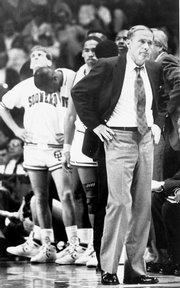 Oklahoma coach Billy Tubbs, right, and his Sooners hang their heads late in their 83-79 championship game loss to the Jayhawks.