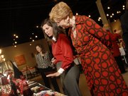 Alice Brewer, Lawrence, a Go Red for Women committee member, foreground left, and Jerelyn Kaesler, Lawrence, view silent auction items Thursday, Feb. 14, 2008, as they participate in the Go Red Women luncheon at Maceli's.