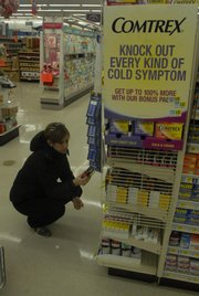 Jennifer Colaner, of Lawrence, looks through the many varieties of cold medicine Friday at Hy-Vee, 31st Street and Kasold Drive. An especially harsh flu season has hit across the nation, including in Lawrence, causing many to miss work and school.