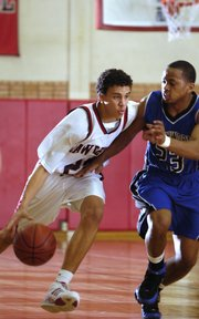 Lawrence High junior Dorian Green, left, brings the ball down court against Leavenworth's Caprest Rhone. Leavenworth topped Lawrence, 54-52, Friday at LHS.