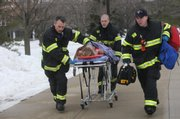 Rescue workers, including Travis Karr, a Free State High School graduate, center, evacuate a victim of a shooting Thursday at Northern Illinois University in DeKalb, Ill. Travis Karr is the son of Jerry Karr, a longtime Lawrence firefighter who retired in 2006.