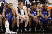 Duke players, from left, Gerald Henderson, Kyle Singler, Lance Thomas and DeMarcus Nelson watch the end of their game against Wake Forest after each player fouled out during a college basketball game in Winston Salem, N.C., Sunday. Wake Forest won 86-73.
