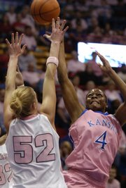 Kansas University's Danielle McCray (4) puts up a shot over Nebraska's Danielle Page. McCray had 10 rebounds and 13 points, including the game-winning free throw, in the Jayhawks' 62-61 victory Sunday in Allen Fieldhouse.