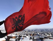 A Kosovar Albanian man holds an Albanian flag on his rooftop Sunday over the ethnically divided town of Kosovska Mitrovica, Kosovo, as he celebrates the independence of Kosovo. Kosovo's predominantly ethnic Albanian leadership proclaimed independence from Serbia on Sunday with Western backing. Serbia has had no formal control over Kosovo, whose population is 90 percent Albanian, since NATO bombing drove out Serb forces in 1999 to halt the killing and ethnic cleansing in a 2-year war against separatist rebels.