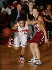 Lawrence High's Jasmyn Turner, left, steals a possession from SM North's Abby Wicinski. Lawrence won, 60-51, Tuesday at LHS.