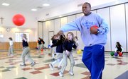 Kansas University basketball guard Russell Robinson releases a dodge ball toward the opposing team of second-grade boys during a game of prison ball Tuesday at Corpus Christi Catholic School, 6001 Bob Billings Parkway. Robinson, along with fellow KU guards Chase Buford and Conner Teahan, also signed autographs for the students and answered a variety of questions during their visit.