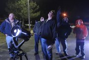 Rick Heschmeyer, second from right, points out various points of the solar system to Gary Weishaar, left, Brian Walter, Greg Yowell and Michael Heschmeyer during a viewing of the lunar eclipse Feb. 20, 2008, in the parking lot of First Presbyterian Church, 2415 Clinton Parkway.