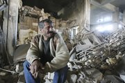 Abbas Hussein sits in the ruins of his shop Friday in central Baghdad. A bomb planted under a horse pulled cart exploded, killing at least three and destroying some shops