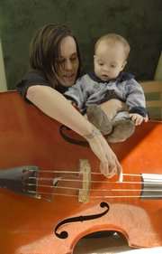 Katie Euliss plays the bass with her son, Julian, 8 months old. Euliss and her husband, Mike West, are the bluegrass duo Truckstop Honeymoon, and they home-school their children so they can be with them as they tour.