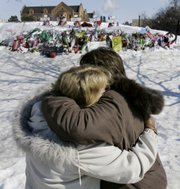 Mourners Doris Kalinoski, left, and Addie Meiser, of Sycamore, Ill., hug Saturday near a memorial to the five students who were killed during the Valentine's Day shooting at Northern Illinois University in DeKalb, Ill.