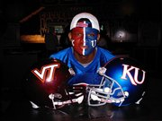 KU fan Jules Hodge took a picture next to the team helmets at the tailgate party at the Orange Bowl in Miami.