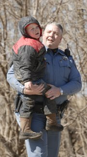 Douglas County Sheriff's Deputy Doug Woods carries a young boy who was reported missing before 11 a.m. Wednesday, February 27, 2008.