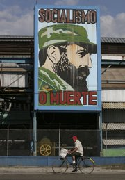 "A cyclist rides past a billboard, with an image depicting Cuban leader Fidel Castro, that reads in Spanish ""Socialism or death""on Tuesday in Havana. Despite talking about a vacation and retirement since resigning as president, Castro retains considerable political power."