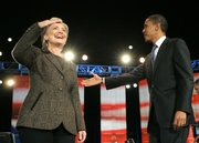 Democratic presidential hopefuls Sen. Hillary Rodham Clinton, D-N.Y., left, and Sen. Barack Obama, D-Ill., enter the stage during their debate Tuesday in Cleveland.