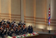 Members of the New York Philharmonic perform Tuesday next to a North Korean flag on stage in Pyongyang, North Korea.