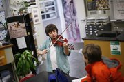 "Sam Thomas, 10, practices ""Amazing Grace"" on the violin Saturday at the County 4-H Club Days at South Junior High School. On the right is his friend, Tristan Tooley, 11. Sam is from the Four Leaf Clover 4-H Club of Douglas County. He has been playing violin for 2 1/2 years."