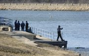 Douglas County Sheriff's deputies inspect the beach and docks at Lone Star Lake on Saturday afternoon after a 67-year-old man drowned after his boat capsized. A second person in the boat was treated for hypothermia and released from the scene.