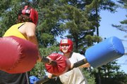 Alexandra Hagemann, 19, right, jousts with an unidentified participant on an inflatable jousting arena last August at the alumni field at a Wellspring New York camp at Paul Smiths College, Paul Smiths, N.Y.