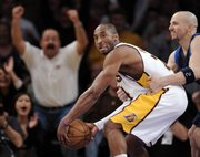 Los Angeles Lakers guard Kobe Bryant, left, is intentionally fouled by Dallas' Jason Kidd in the final seconds of overtime. Bryant scored 52 in the Lakers' 108-104 victory Sunday in Los Angeles.