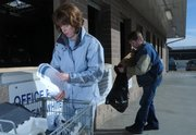 Lawrence residents Debbie Galbraith and Joel Wasson make their way down the line depositing their recyclables Tuesday at the Wal-Mart Recycling Center, 3300 Iowa. The city of Lawrence offers many resources for those who wish to recycle.