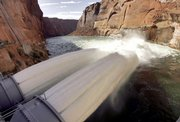 Water flows from two jet tubes Wednesday at Glen Canyon Dam in Page, Ariz. The Department of Interior is experimenting with high flows of water from the dam to help, in part, rebuild beaches along the Colorado River that runs through the Grand Canyon.