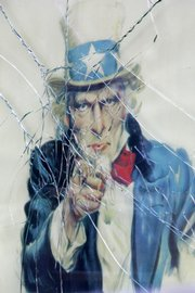 The image of Uncle Sam is seen behind shattered glass at the military recruitment center Thursday in New York's Times Square.