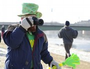 Lawrence resident Jerry Henley snaps a photo of a runner participating in the 5k Shamrock Shuffle during a blistery Saturday morning along the Kansas River levee.  Henley, who dressed up for the morning festivities, was one of a handful of onlookers who rooted for the runners as temperatures hovered in the teens.