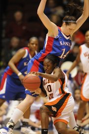 Kansas University's Krysten Boogaard (14) tries to slow Oklahoma State's Andrea Riley. Riley scored a game-high 23 points as the Cowgirls routed KU, 82-62, in a Big 12 tournament quarterfinal game Wednesday at Municipal Auditorium in Kansas City, Mo.