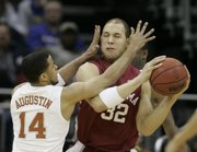 Texas guard D.J. Augustin (14) defends Oklahoma forward Taylor Griffin (32). The Longhorns pummeled the Sooners, 77-49, Saturday in Kansas City, Mo.