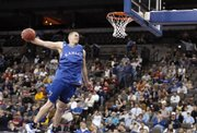 Kansas center Cole Aldrich soars to the bucket for a windmill dunk before a crowd of Jayhawk fans. KU held a short, public workout Wednesday, the eve of today's NCAA Tournament opener against Portland State.