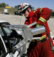 "A Hillsborough County firefighter opens up a car&squot;s door during a ""Jaws of Life"" demonstration recently in Tampa, Fla. Today&squot;s cars save lives by cocooning motorists in reinforced alloys, impact-absorbing crumple zones and as many as a dozen air bags. But rescue officials and experts from around the United States say the new technology is also hindering extrication of injured people."