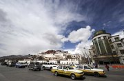 In this photo released by China's Xinhua News Agency, traffic flows Wednesday in front of Potala Palace, the former residence of the Dalai Lama, background left, in Lhasa, capital of southwest China's Tibet Autonomous Region. Chinese authorities are regaining control of Tibetan areas following massive protests that began last week.