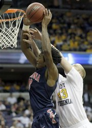 Arizona forward Jordan Hill stretches for the basket under pressure from West Virginia center Jamie Smalligan during the second half of a first-round NCAA men's basketball tournament West Regional game Thursday, March 20, 2008, in Washington.