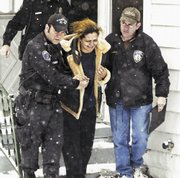 Officer Manuel Espinoza, left, and detective Peter Vambaketes, right, of the Alton (Ill.) Police Department, help Michelle Riley from a house in Alton after the body of Dorothy Dixon, 29, was found inside in this photo taken Jan. 31. Dixon, who was developmentally disabled and pregnant, was later determined to have been tortured to death. Riley was one of six people - two adults, three teenagers and a 12-year-old boy - charged with murder in the case.