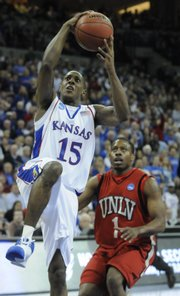 Kansas guard Mario Chalmers heads to the bucket past UNLV guard Wink Adams after a steal during the first half Saturday, March 22, 2008 at the Qwest Center in Omaha, Nebraska.