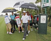 Tiger Woods, center, and Geoff Ogilvy, back left, prepare to leave the golf course on the 12th tee after a weather delay Saturday in Doral, Fla. Ogilvy leads the CA Championship by one stroke over Adam Scott. Woods is three strokes back.